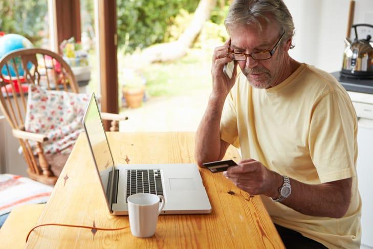 hombre con barba y gafas en camiseta amarilla sentado a la mesa con computadora y tarjeta de crédito, en el teléfono.