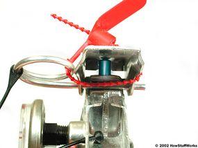 La palanca de operación empuja hacia abajo una varilla de accionamiento (la pieza azul).
